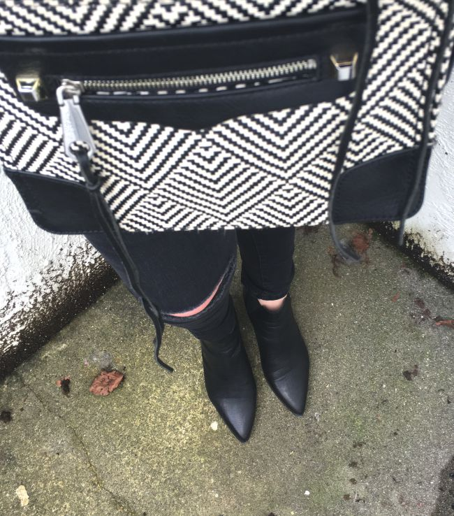 blogger wearing ripped jeans and black boots