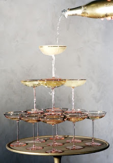stack of champagne glasses with bottle of champagne pouring from top