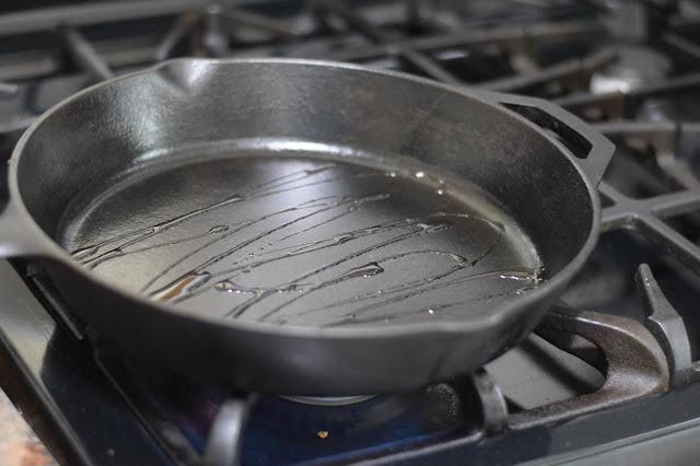 A cast iron skillet on the stove with oil in it.