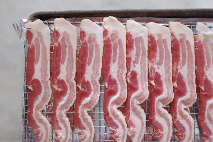 bacon on cooling rack on baking sheet ready to bake