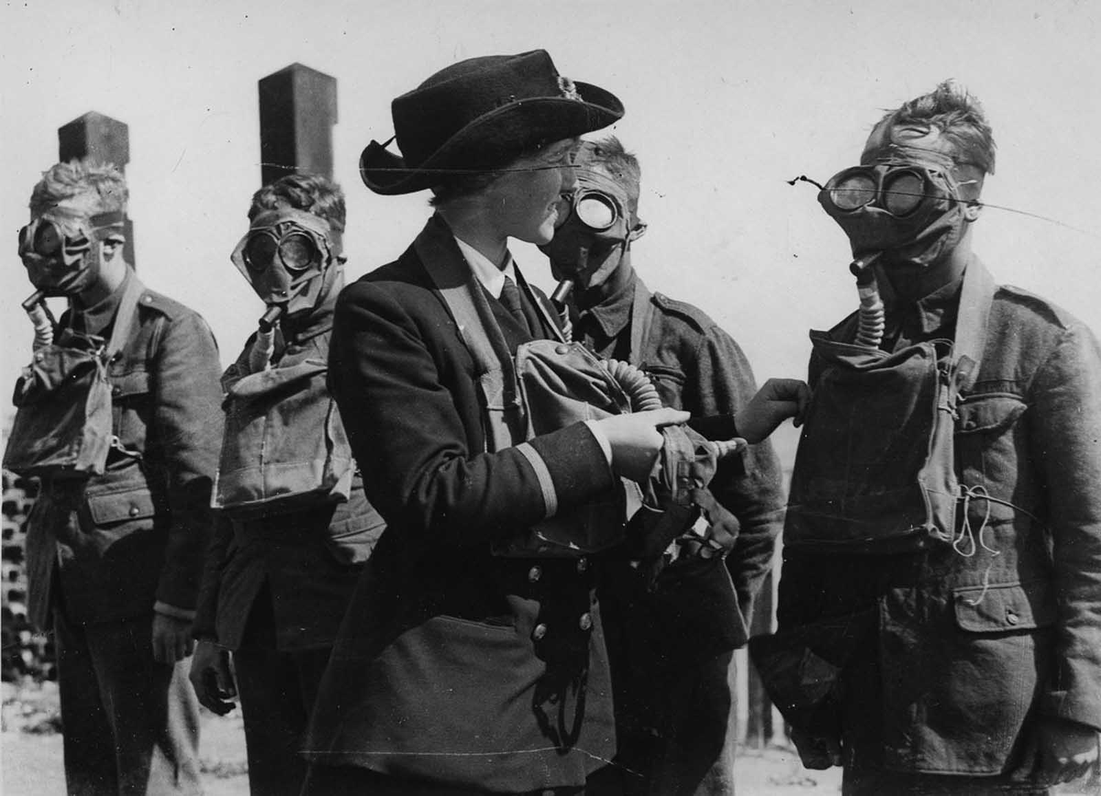 A Women's Royal Naval Service instructor drills recruits with gas masks.
