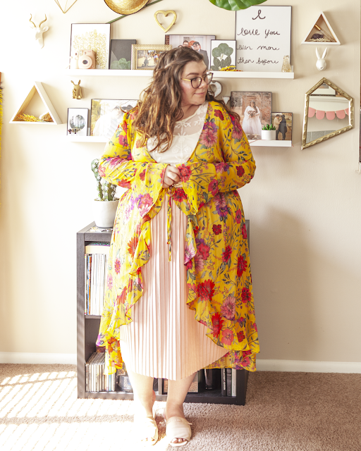 An outfit consisting of a yellow floral long sleeve robe with bell sleeves and ruffles at the hem belted over a white lace blouse tucked unto a pastel pink pleated skirt with pastel pink slide sandals.