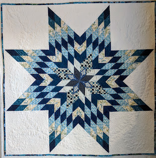 Traditional Lone Star quilt of blue and white fabrics set on white background with feather quilting