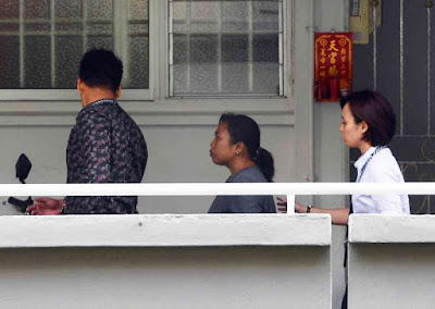 Indonesian maid Minah  (center) now charged with the murder of her employer.