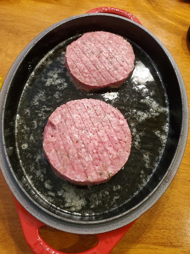 there are two lamb patties in a grill pan made by Le Creuset ready to cook