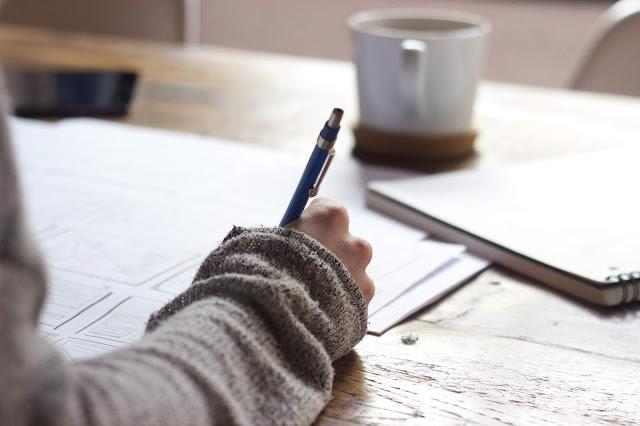 Mãos femininas escrevendo em uma folha em cima da mesa