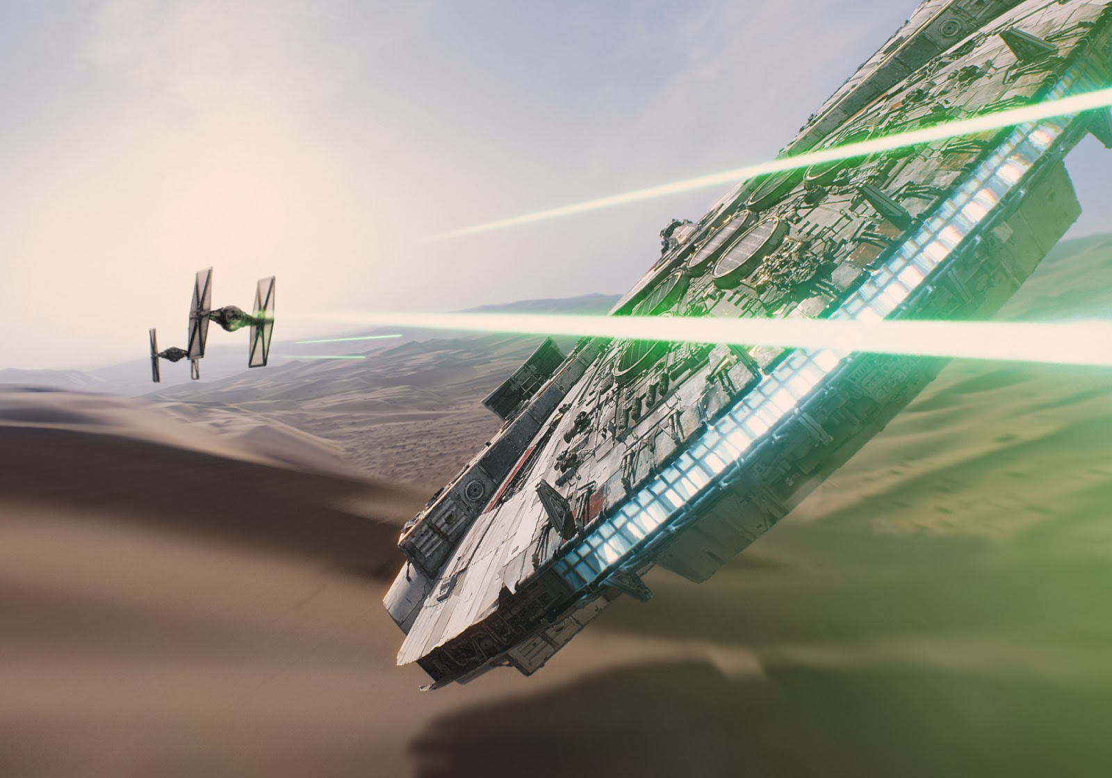 The Millenieum Falcon, flying over a desert, takes on two TIE Fighters.