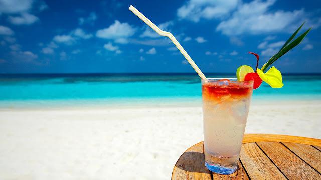 Cocktail op een tafeltje op het strand bij de zee