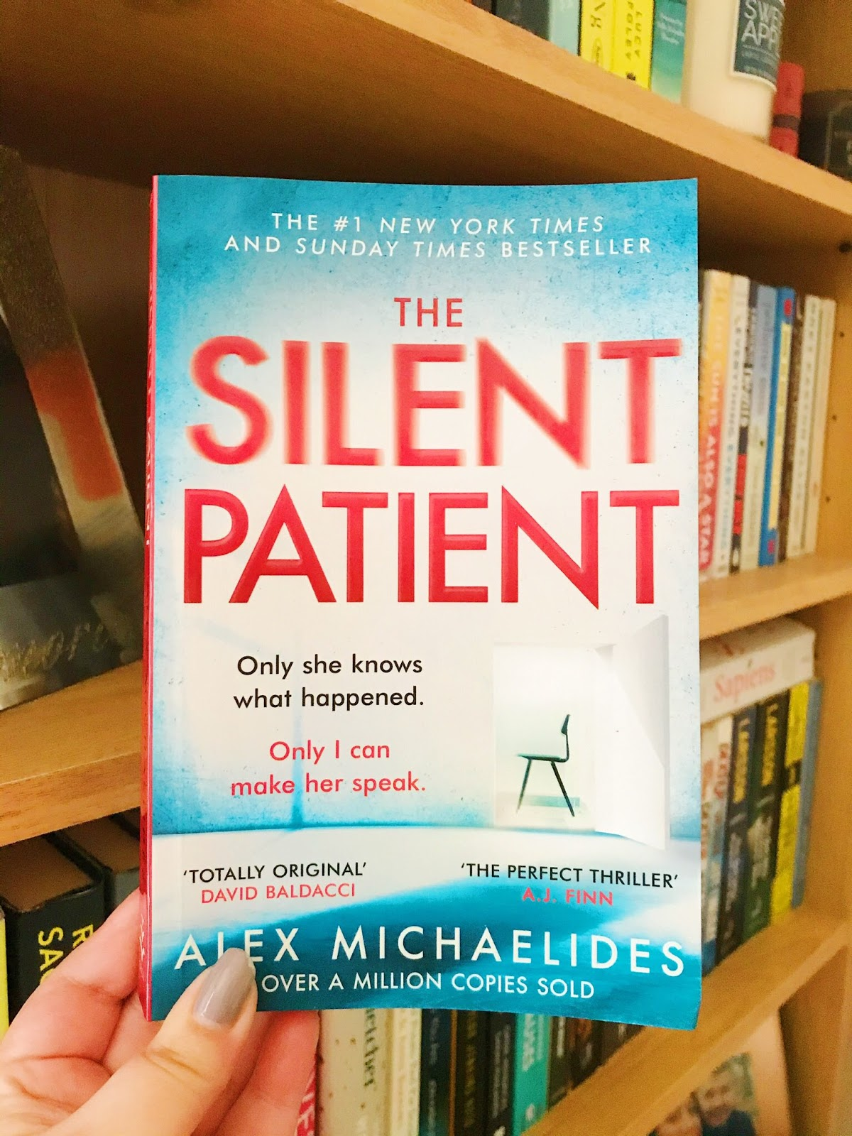 The Silent Patient book held up in front of bookshelf