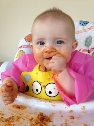 A baby in a padded highchair, pink overall and yellow bib eating a tomato rice dish with their hands