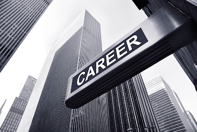 """black and white photo of a city street corner.  Sign in forground that reads: """"career."""""""