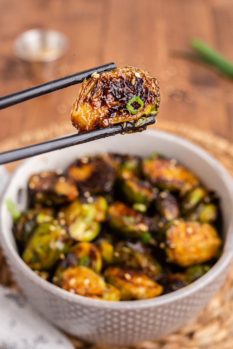 Closeup photo of Kung Pao Brussels Sprouts in a white bowl with someone holding one sprout with chopsticks.