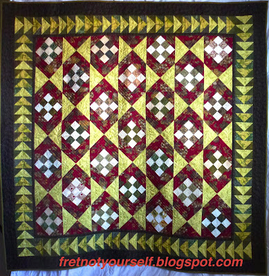 Simple khaki and white nine-patches on point alternate with dark red and chartreuse hourglasses to create the design of this quilt. A chartreuses and dark green inner border is followed by a dark brown outer border.
