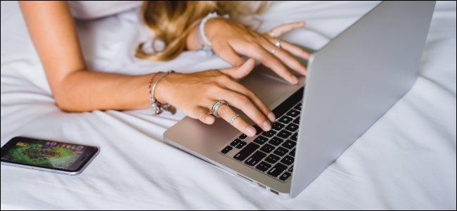 امرأة تستخدم جهاز MacBook على سرير ، وهو أمر سيئ للتبريد.