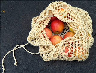 A drawstring bag mesh bag left partially open. The bag has apples inside.