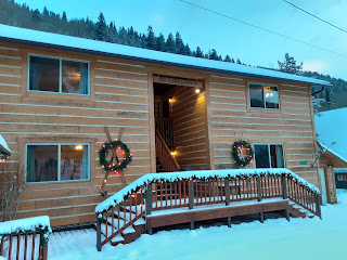 Exterior mountain lodge with garland and Christmas wreaths.