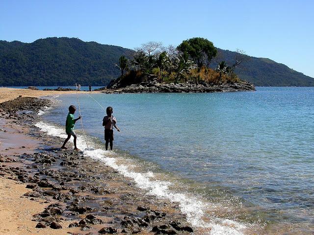 des gamins pêchent sur la plage avec une canne de leur invention
