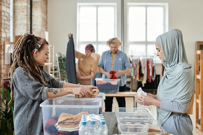 A woman in dreadlocks and a woman in a hijab looking through bins of merchandise at a store.
