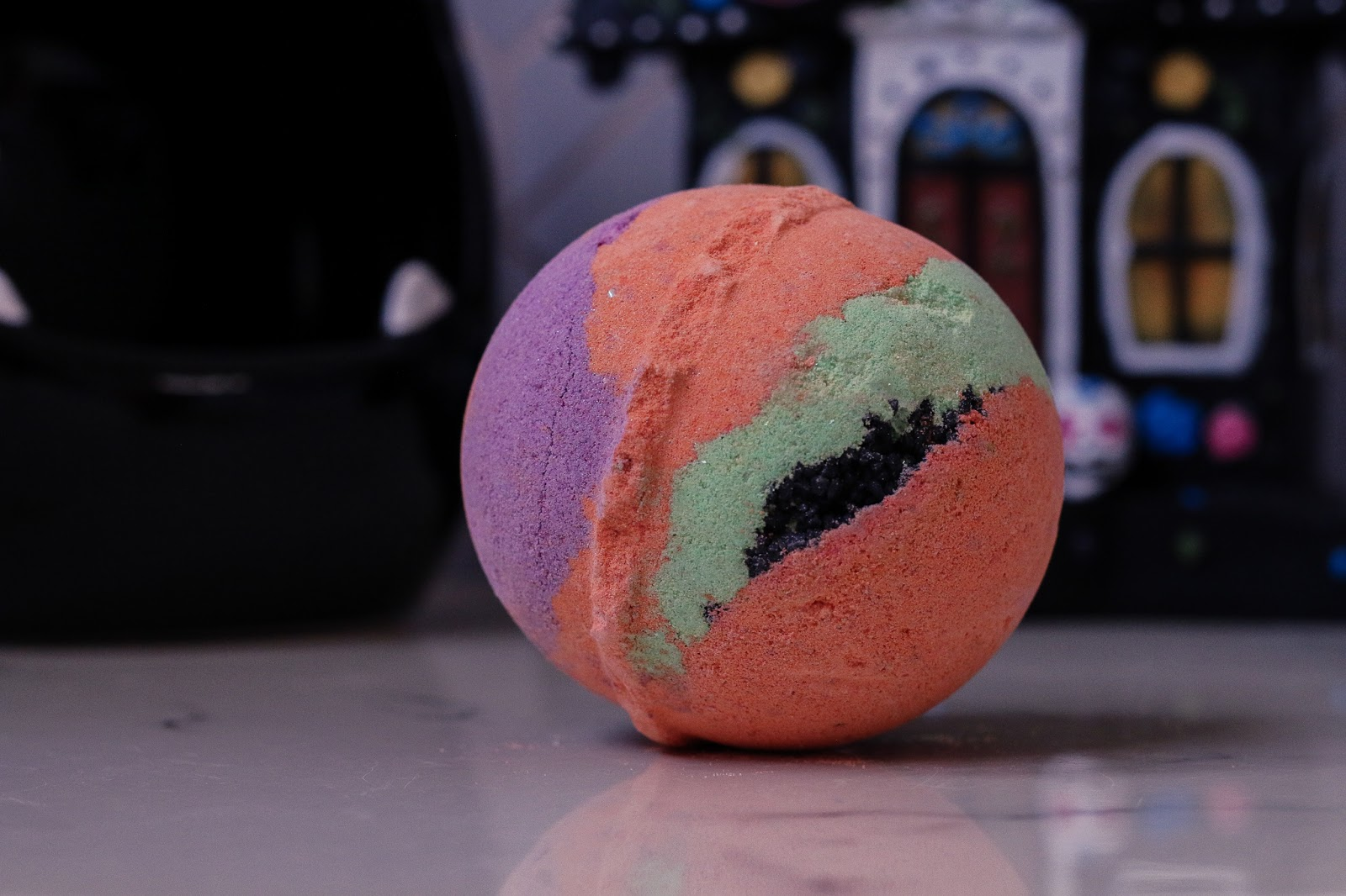 extreme close up photo of the Mercury Retrograde Bath bomb from lush. A round orange bath bomb with green, purple and black coarse sea salt through it. Bath bomb sitting on white marble bed side table with a Haunted house Halloween decoration in the background.