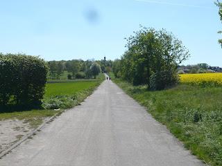 Ein langer Weg, der leicht bergauf führt. Rechts ein gelbes Rapsfeld, links eine grüne Wiese