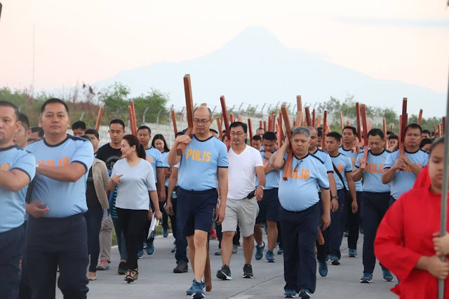 Police Regional Office (PRO) 12 Reg'l Dir. PBGen. Eliseo Tam Rasco carries his cross during police via crucis on Good Friday.