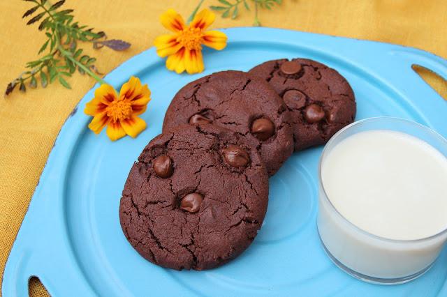 Sinisellä tarjottimella on lomittain kolme suklaista keksiä sekä pieni lasillinen kauramaitoa. Tarjottimelle on aseteltu myös kaksi keltaista kehäkukkaa.