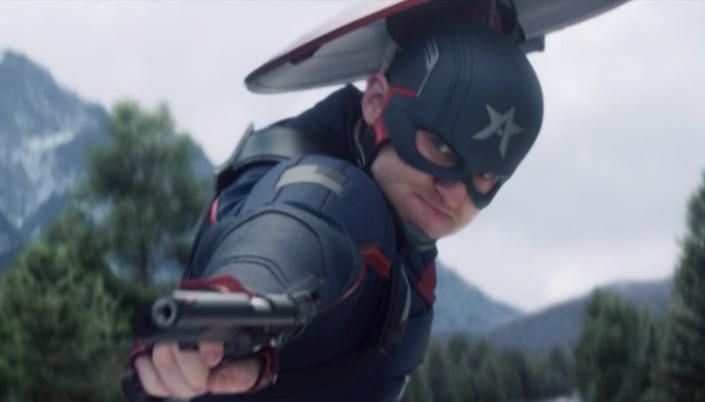 Imagem: o Agente Americano no uniforme de Capitão América azul com um A no seu capacete, o escudo, apontando um pistola durante uma luta em cima de um caminhão e ao fundo uma paisagem de floresta.