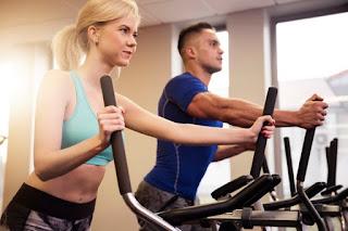 casal jovem fazendo treino elíptico na academia