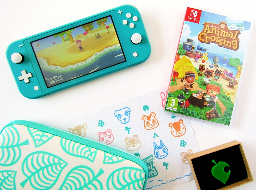 A flatlay photo taken from above showing a teal Nintendo Switch games console with Animal Crossing New Horizons on screen, a green leaf acrylic brooch, an Animal Crossing New Horizons case, an Animal Crossing character print microfibre cloth, and a leaf print Animal Crossing New Horizons Switch case on a white background.