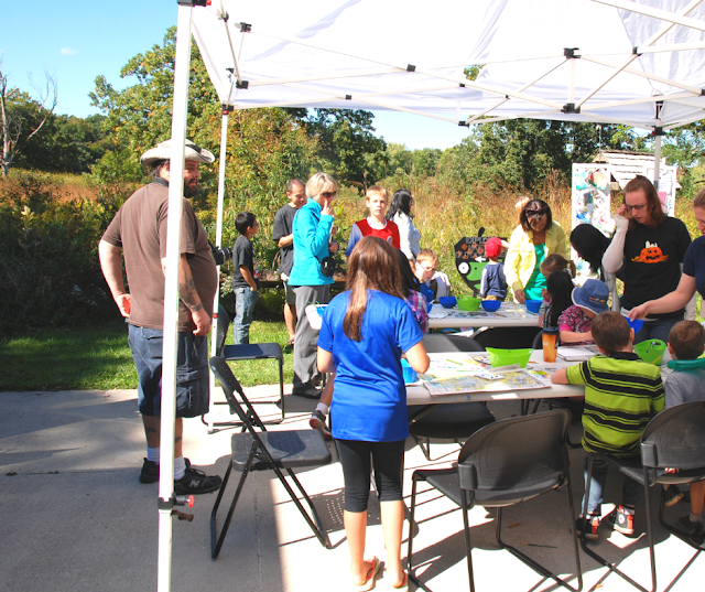 Families engaging in art experiences in the stunning nature of Crabtree Nature Center during Art in Nature. Image credit Artistic Journeys.