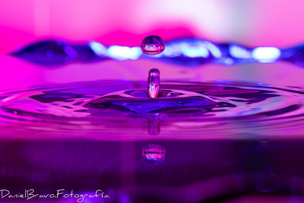 Fotografía de una gota de agua y su salpicadura, con colores de fondo más intensos en tonos rosas y azules