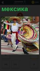 на улицах Мексики танцуют мужчины и женщины в национальных костюмах
