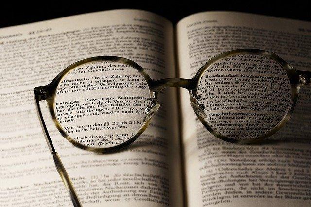Kacamata yang tergeletak pada sebuah kamus