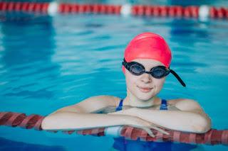 jovem adolescente óculos touca de natação parada na piscina