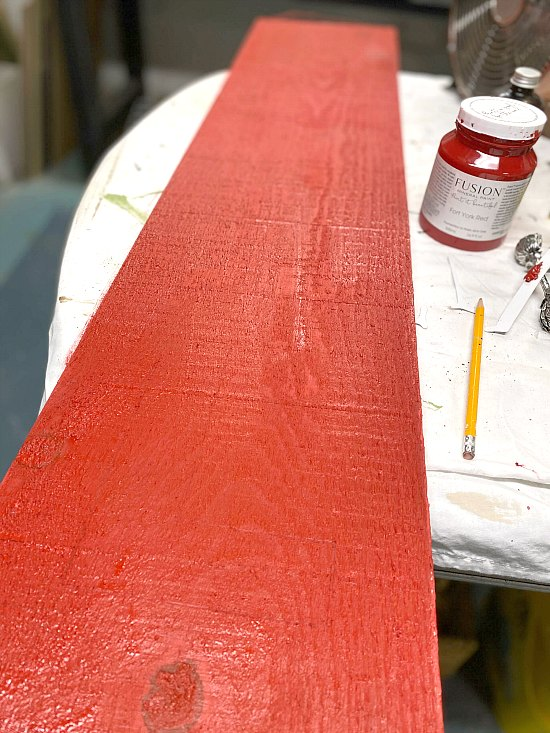 A rough hewn board painted red