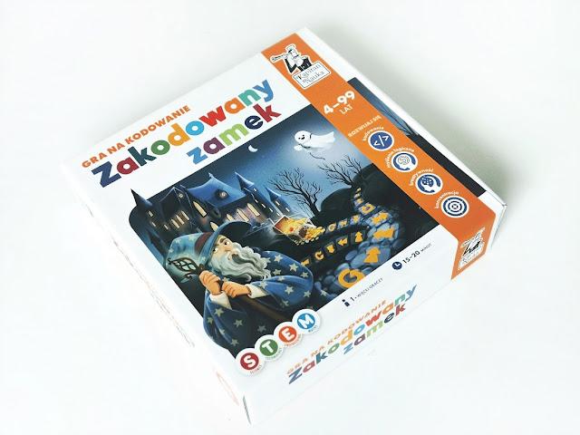 na zdjęciu pudełko gry zakodowany zamek z wizerunkiem czarodzieja na froncie a  w tle widać zamek nocą