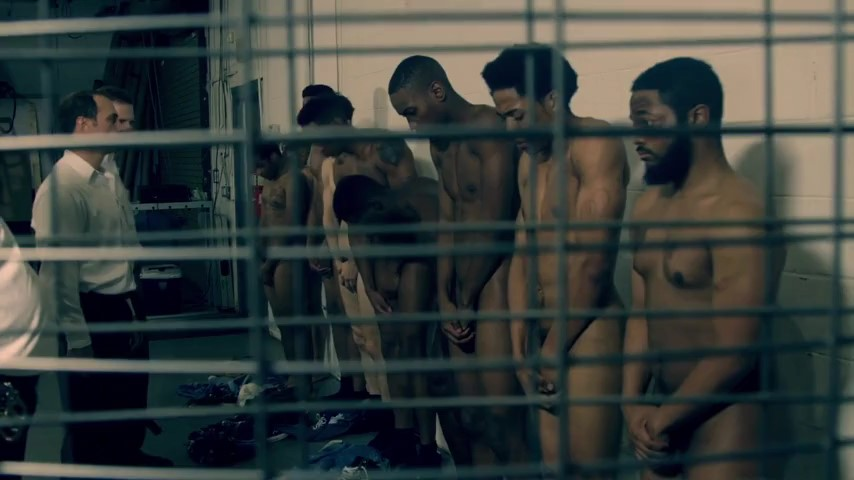 Naked men and young boy in prison shower