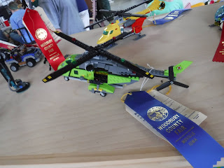 a blue ribbon hangs off a lime green Lego helicopter