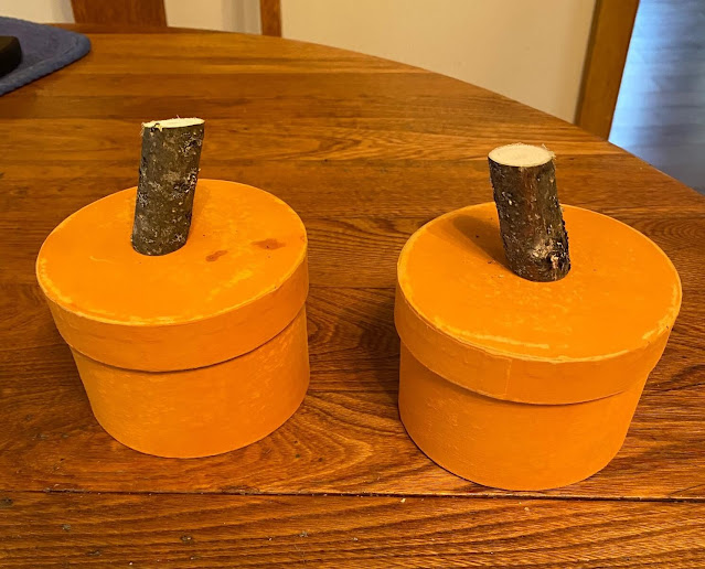 Photo of two round boxes painted orange with wooden stick stems