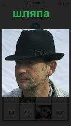 стоит мужчина на голове которого одета темная шляпа