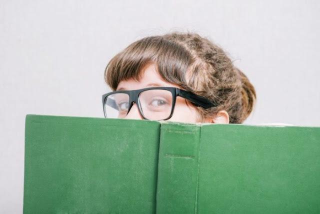 Women hiding behind a book