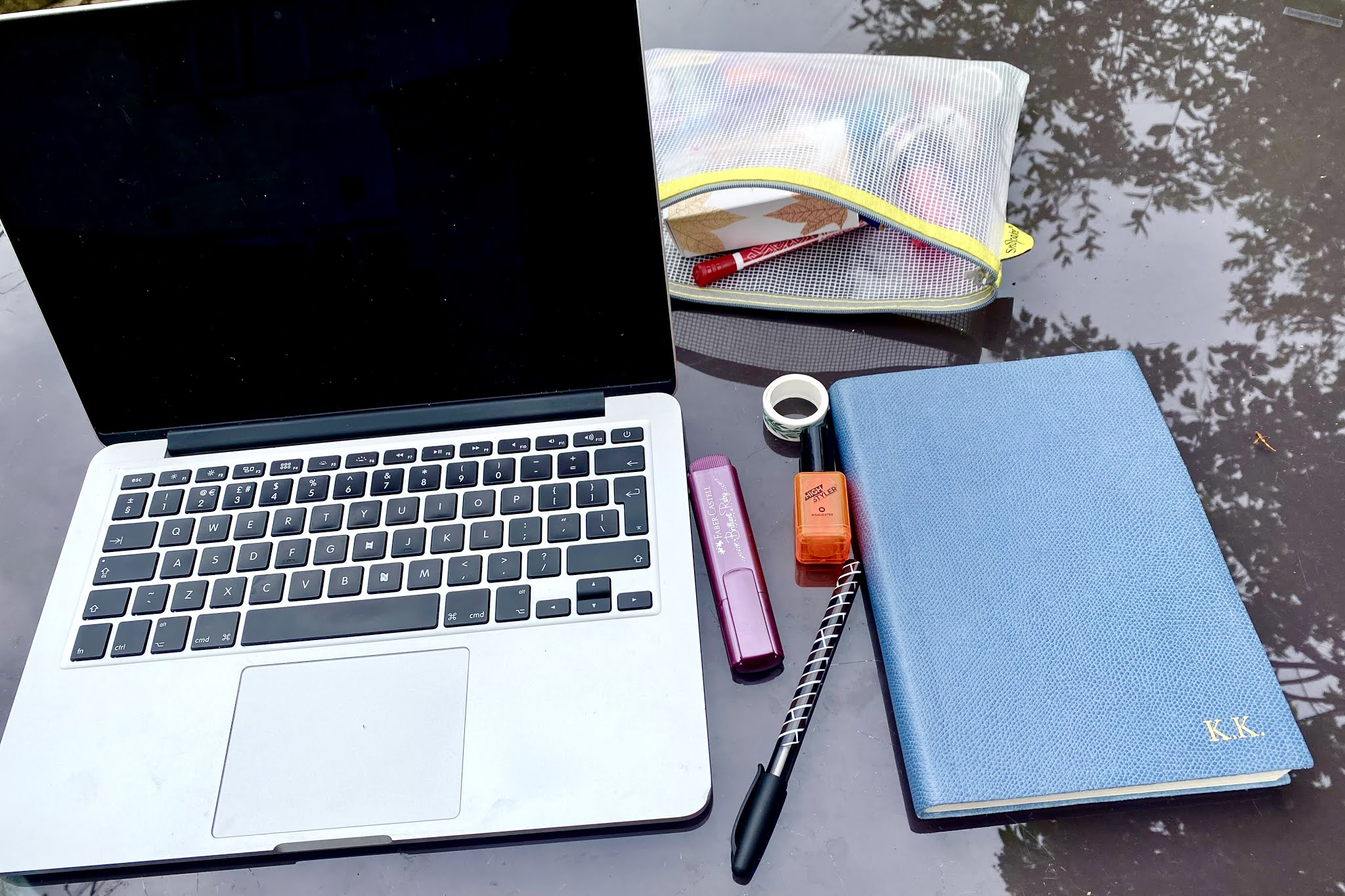 A laptop, note pad and pencil case on a glass garden table with trees reflected in it