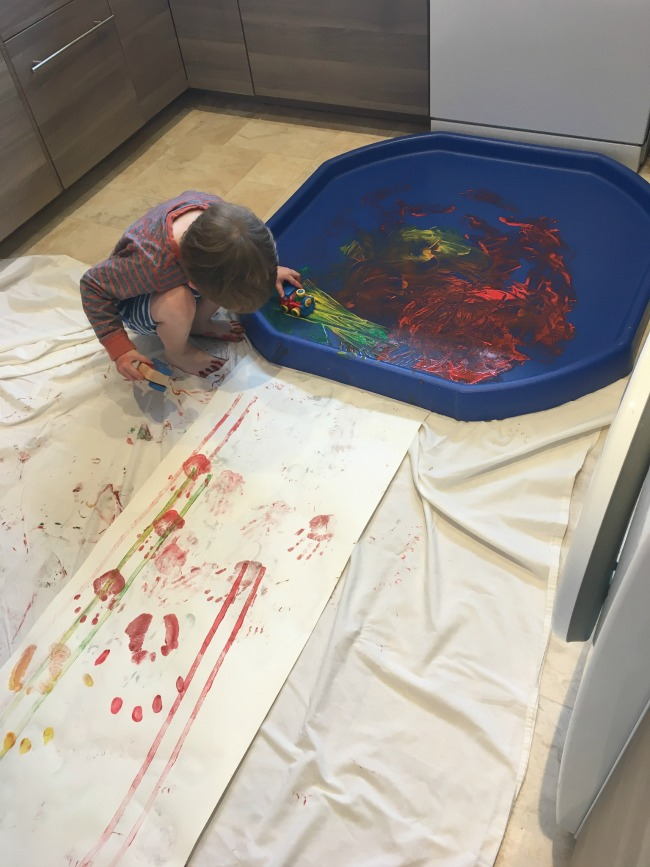 tuff-spot-with-paint-and-roll-of-paper-and-toddler-with-car