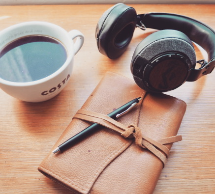 Coffee cup, headphones & leather bound notebook