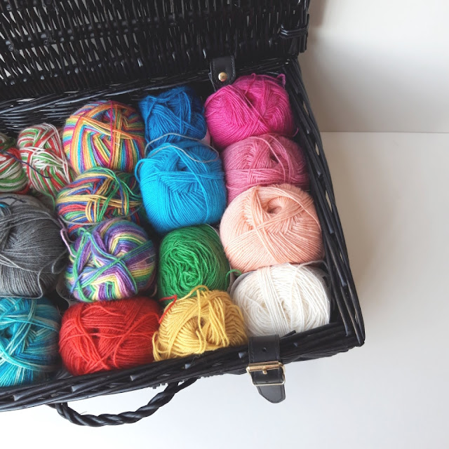 Multi-coloured yarns stored in a brown wicker hamper.  The hamper is open so that you can see the yarns