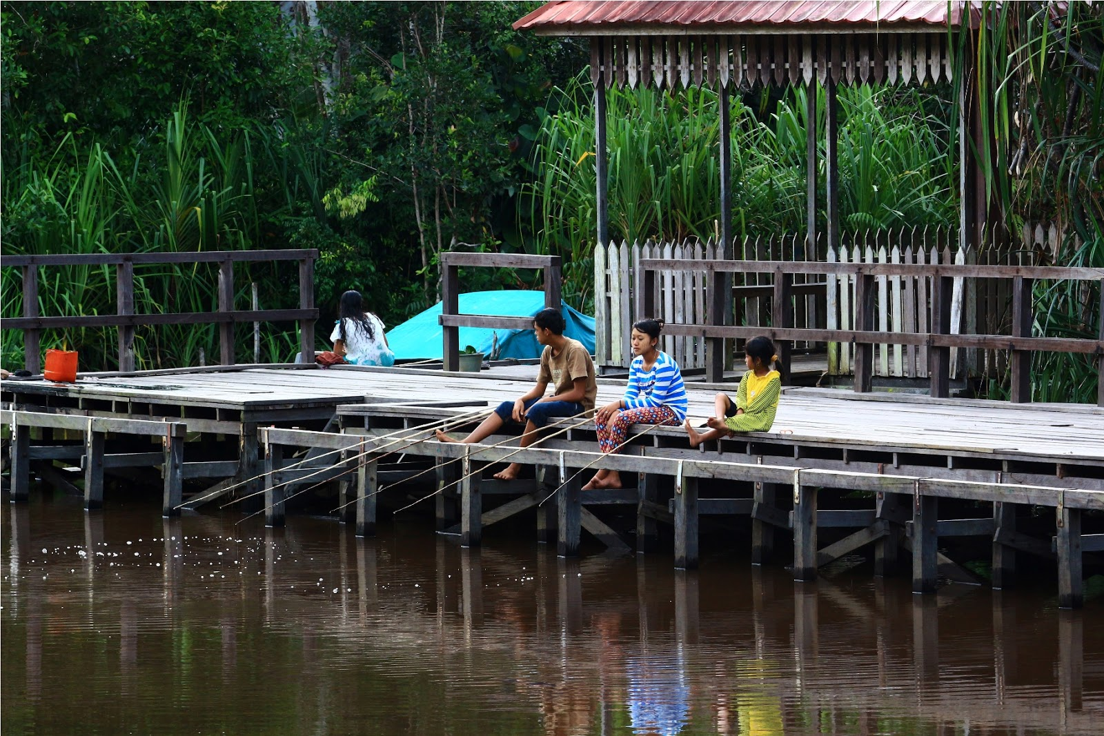 Anak-anak Sungai Sekoyer yang asyik memancing dari dermaga