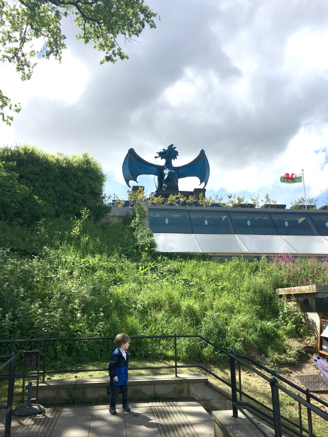 a-toddler-explores-cardiff-castle-world-war-two-shelters-view-of-inside-castle-with-toddler-posing-infront-of-football-dragon-from-inside-the-castle
