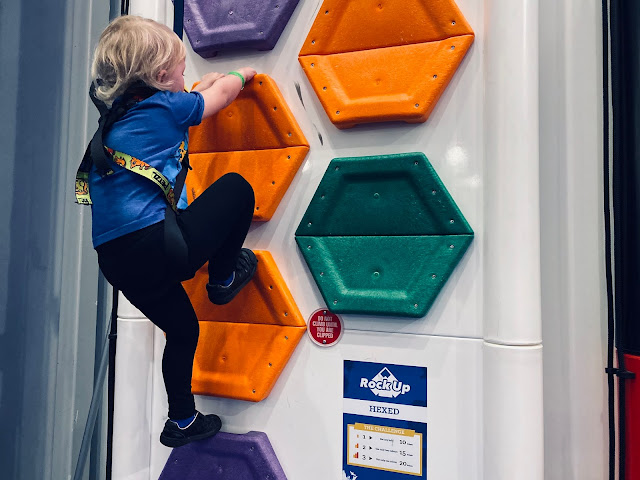 A 4 year old climbing up a climbing wall at Rock Up Lakeside called Hexed which has hexagon shapes to grip onto