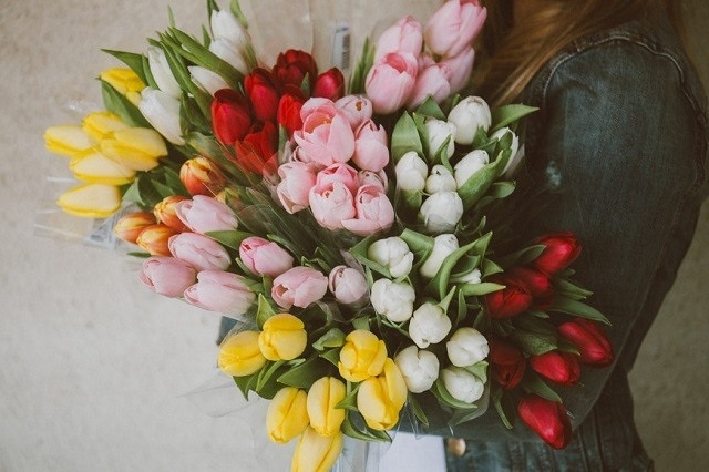 woman holding bouquet of tulips different colors