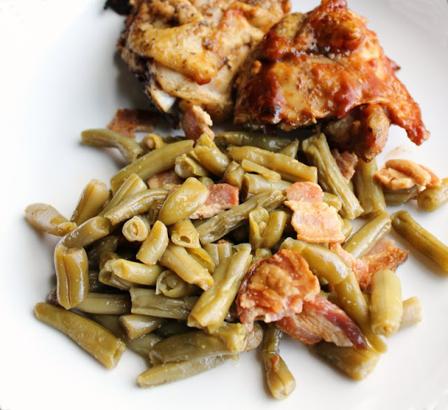close up of smothered green beans with bits of bacon served with bbq chicken in the background